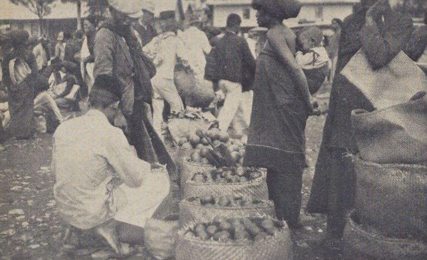 Pemandangan pasar di Berastagi. Karung jeruk di latar depan dengan orang Karo berdiri di dekatnya.